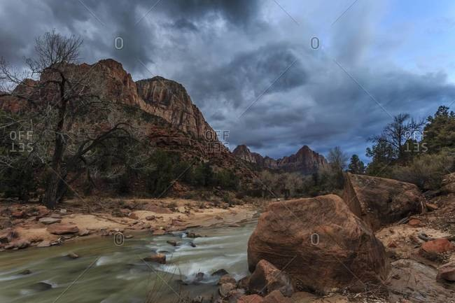 Dusk beside the Virgin River under a threatening sky in winter, Zion National Park, Utah, United States of America, North America