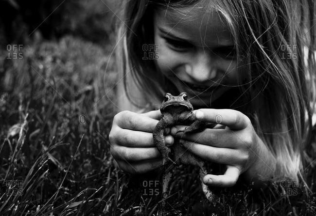 Girl capturing a frog