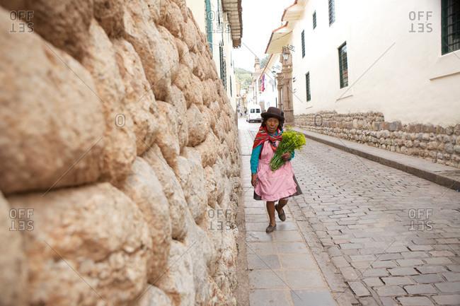 Cusco, Peru - April 5, 2013: An elderly woman holding flower walking along a cobblestone street, Cusco, Peru.