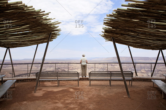 An older woman takes in the view from the rim of Namibia's Fish River Canyon