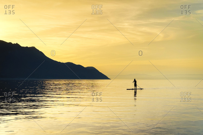 Man on a paddle board on Lake Geneva, Switzerland