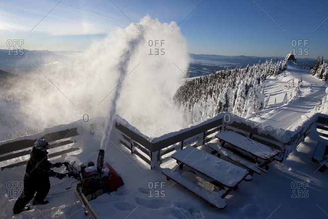 Worker using a snow blower to remove snow from the summit house deck