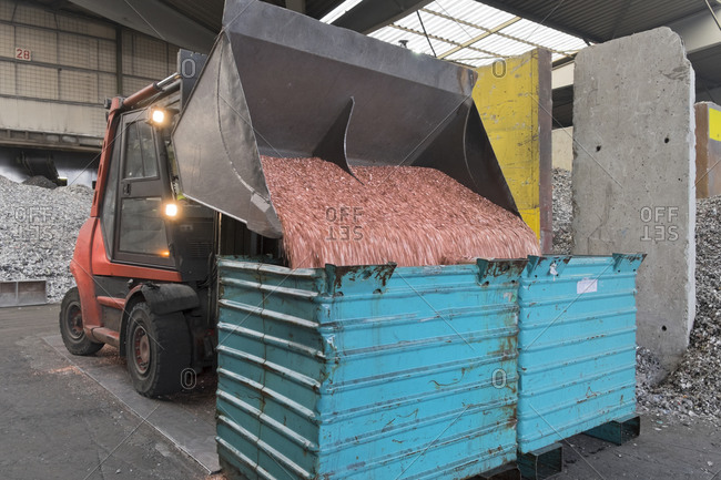 Excavator shovel unloading scrap in a scrap metal recycling plant