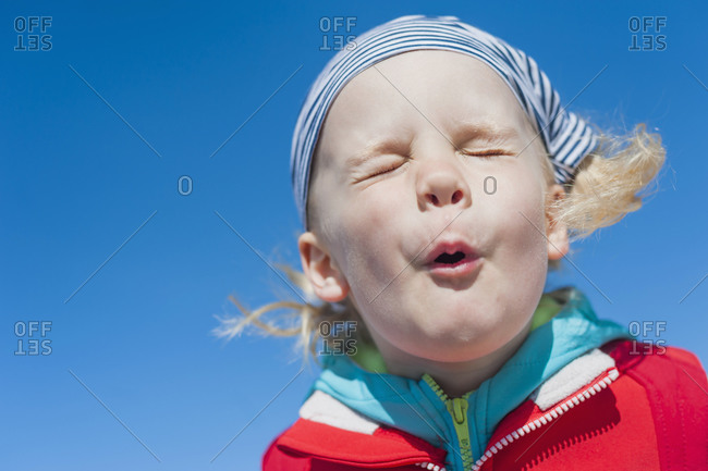 Boy pulling faces under blue sky