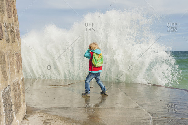 Excited boy standing at the pier with splashing water