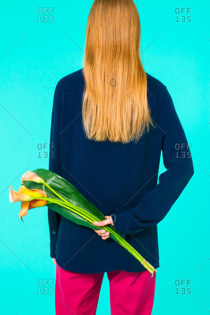 Back view of a woman holding an Calla Lily flower