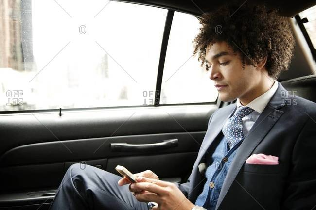 Young businessman checking smartphone in cab