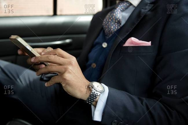 Businessman checking smartphone in cab