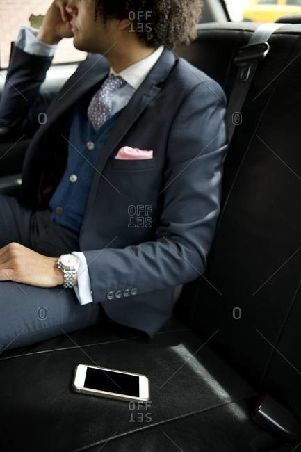 Cell phone beside businessman in cab