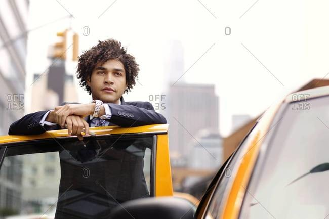 Businessman standing at door of cab, New York City