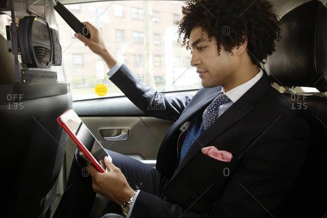 Businessman on tablet in cab