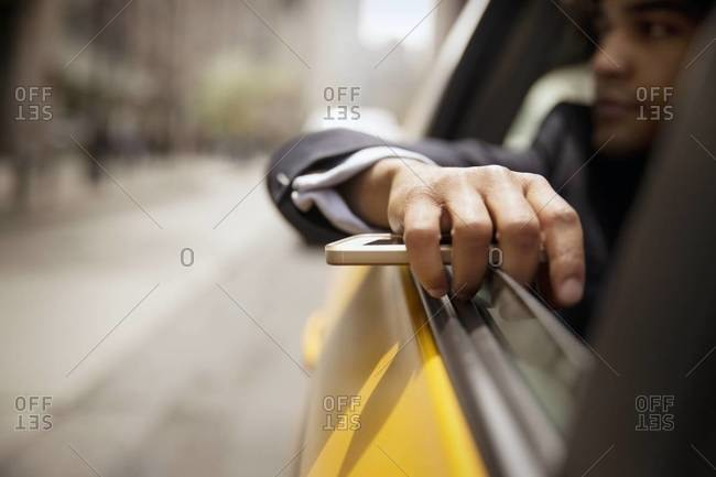 Businessman holds cell phone in cab