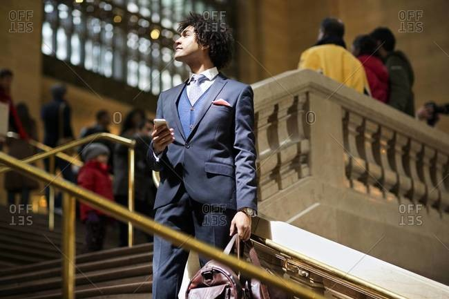 Businessman with valise on steps at Grand Central Terminal, New York City
