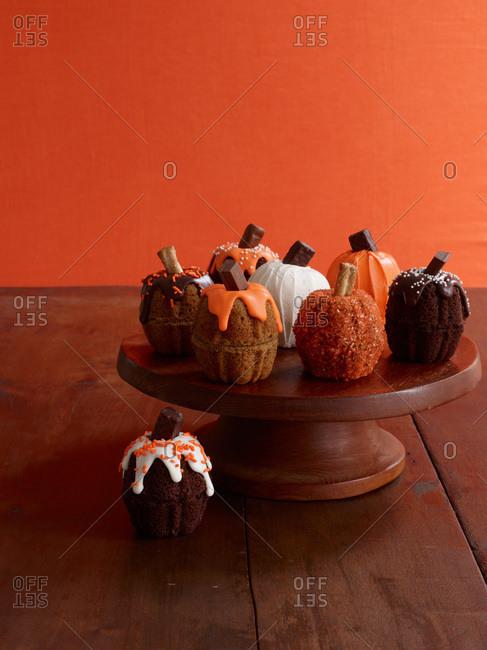 Stylish mini pumpkin cakes on a cake stand