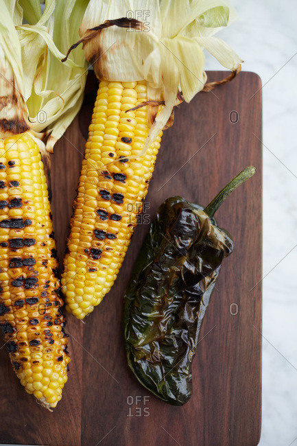 Grilled corns and chile poblano on a cutting board