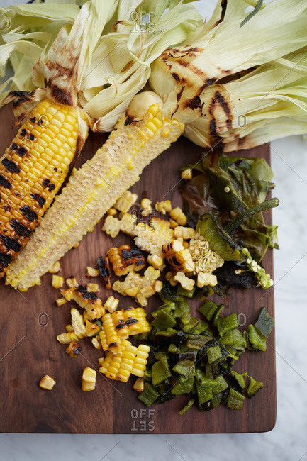 Grilled corn and chile poblano on a cutting board