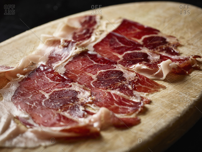 Slices of meat on cutting board over black background