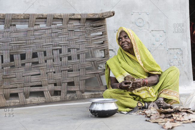 Damoh, India - April 28,2014: Elderly woman making beedi cigarettes in India earning less than a dollar per day
