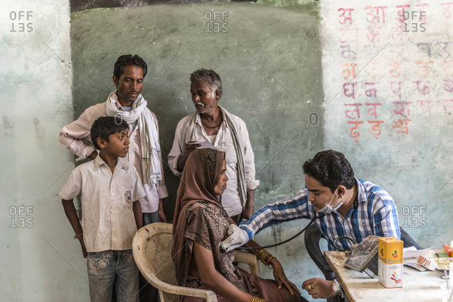Madhya Pradash, India - April 29,2014: Doctor examines a patient at a village medical clinic in India