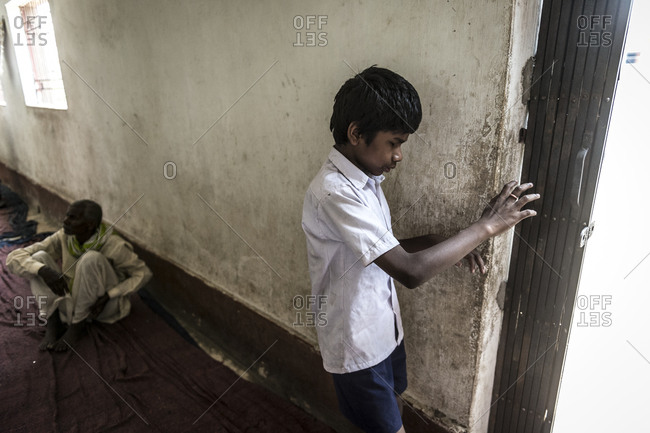 Orissa, India - May 2,2014: Blind Indian young boy reach out for a wall
