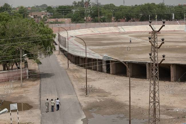 Young men walk to an empty stadium to play cricket in Bikaner, India