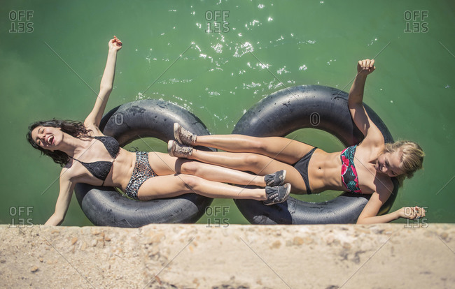 Two young woman floating in inner tubes