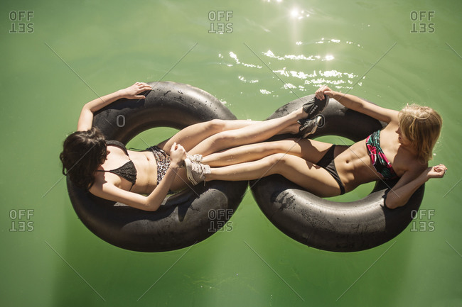 Two young woman holding each other feet while in inner tubes