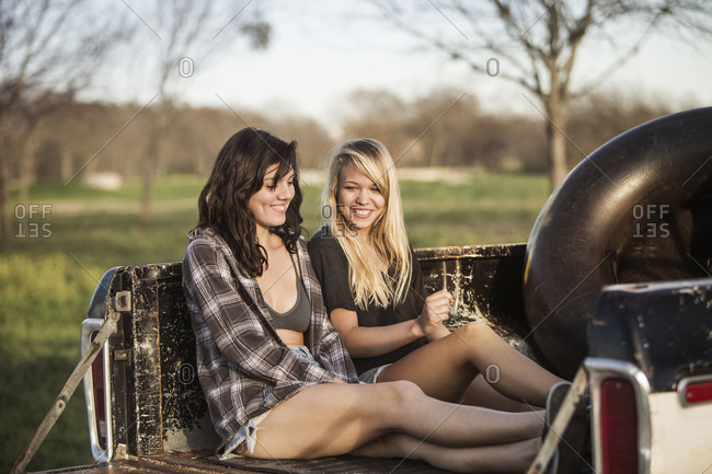 Two girls sitting in the back of a pick up truck