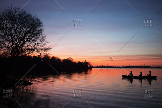 Silhouette of three woman paddling on the lake at sundown