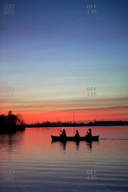 Silhouette of three woman paddling on the lake at sundown
