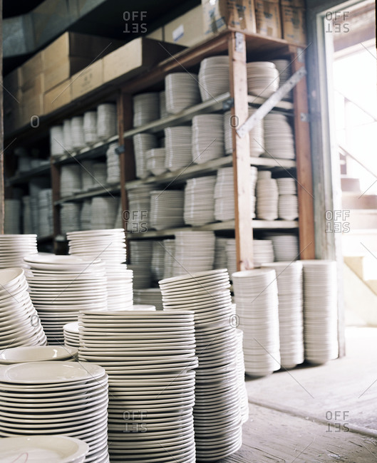 Stacks of white plates in storage