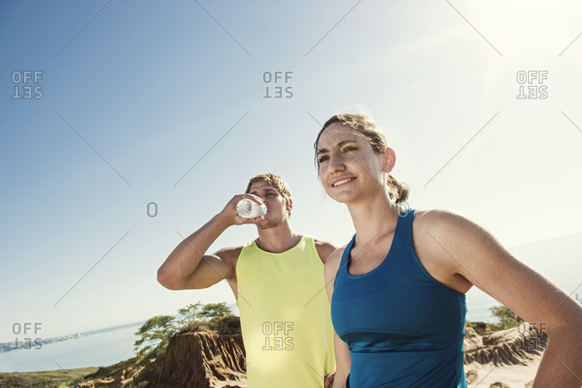 Thirsty runners drinking from a bottle