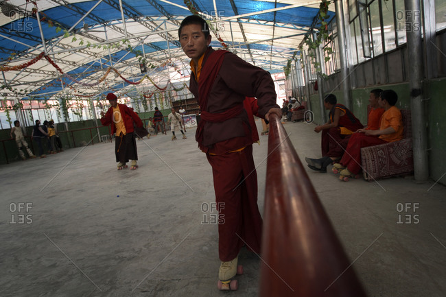 Kyushu, Qinghai Province, China - July 23, 2006: Student Buddhist monk roller skating with friends at a rink in Kyushu, Qinghai Province, China