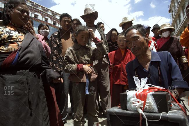 Kyushu, Qinghai Province, China - July 23, 2006: Onlookers watching a street performer in Kyushu, Qinghai Province, China