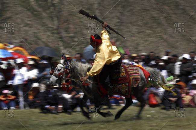 Kyushu, Qinghai Province, China - July 24, 2006: Rider at the Kyushu Tibetan Horse Racing Festival