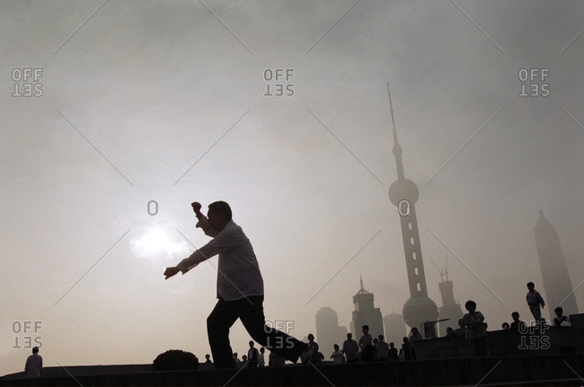 Pudong, Shanghai, China - April 27, 2006: Man practicing Qigongi with Pudong in the background, Shanghai