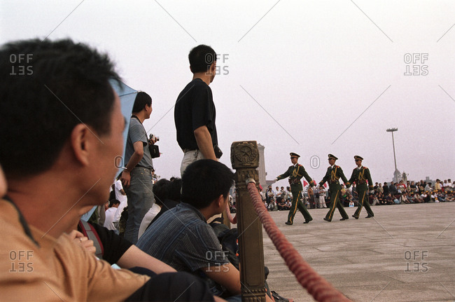 Tiananmen Square, Beijing, China - November 11, 2005: Chinese tourists watch as People�s Liberation Army soldiers perform the daily flag raising ceremony at dawn in Tiananmen Square in Beijing, China