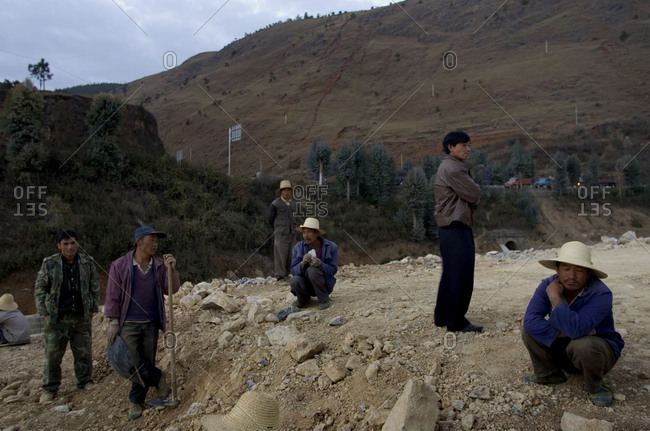 Old Burma Road, Yunnan Province, Southwest China - January 15, 2006: Laborers pause briefly from work as they wait for small demolition explosives to ignite at a construction site for a new highway project in the Yunnan province in southwestern China