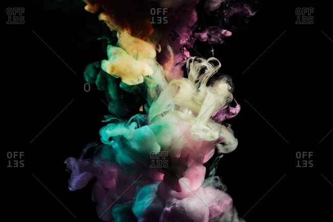 Smoke, reminiscent of circus colors, comes together on a black background.