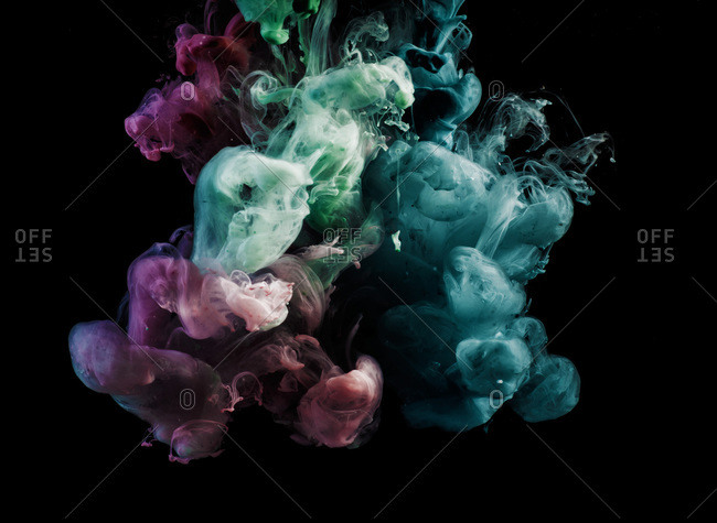 Purple, green, and blue smoke come together on a black background.