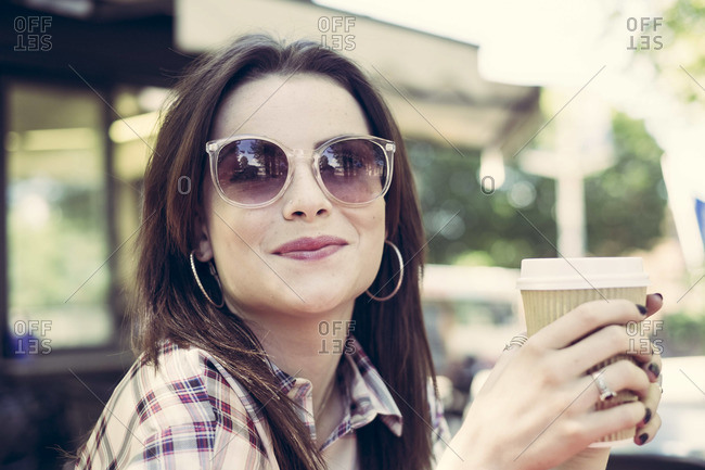 Young woman smiles with coffee