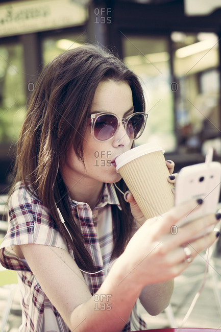 Young woman drinking coffee and checking electronic device