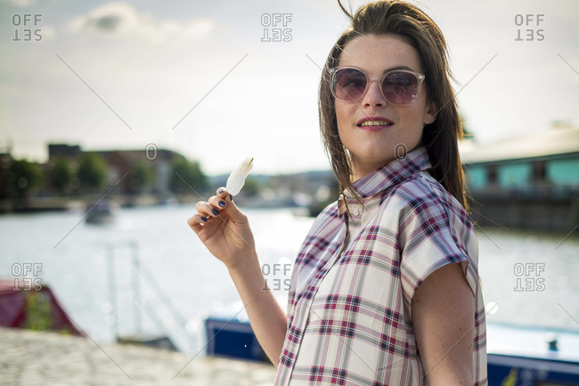 Young woman eating popsicle on the waterfront