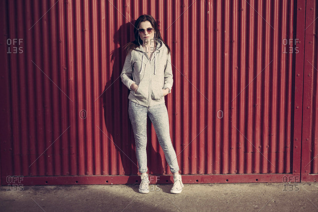 Young woman in hoodie posing in front of metal wall