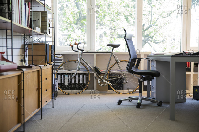 Racing cycle standing at workplace of modern office