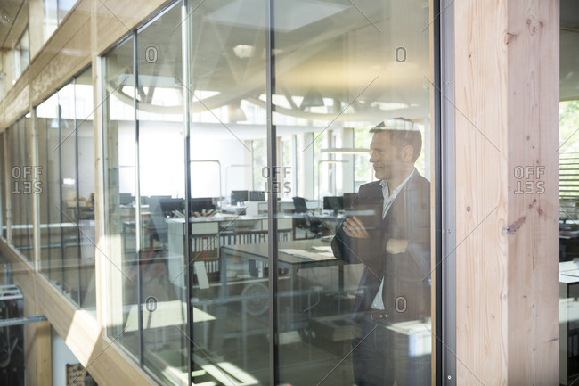 Portrait of business man with crossed arms standing behind glass pane