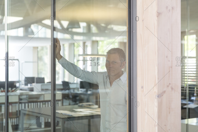 Portrait of smiling creative business man behind glass panel