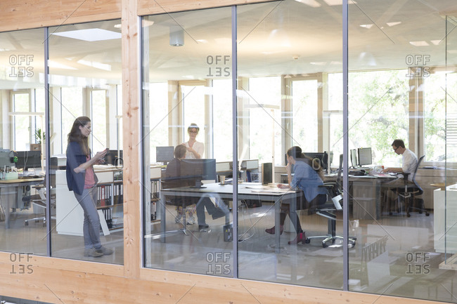 Team of five business people at workplaces in modern office