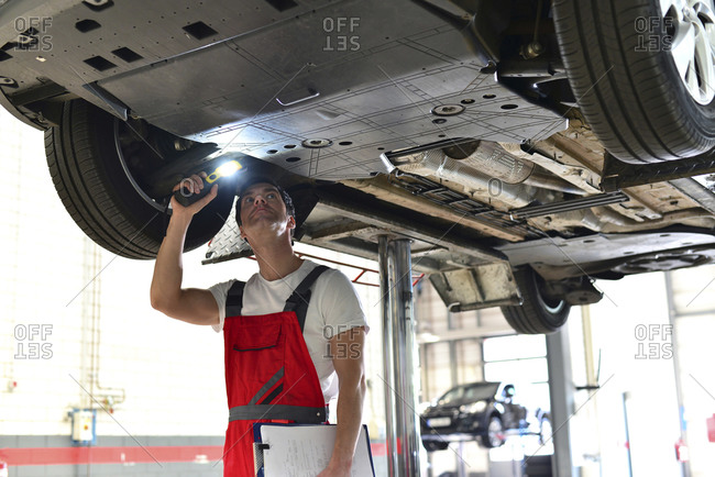 Car mechanic in a workshop checking underbody of a car