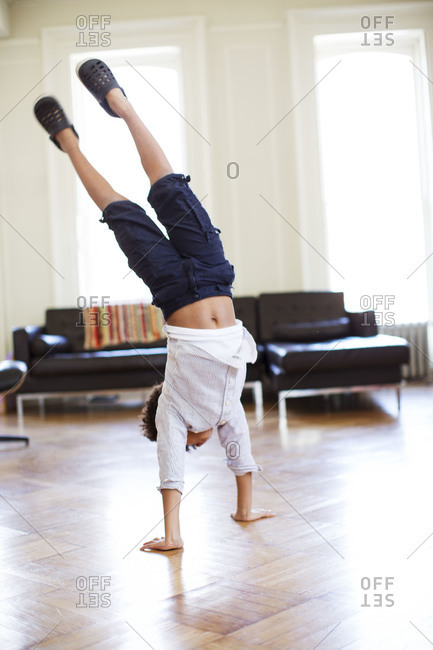 Boy doing cartwheel inside
